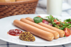 Wiener sausage. Wiener sausage with ketchup, mustard and salad Royalty Free Stock Images