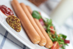 Wiener sausage. Wiener sausage with ketchup, mustard and salad Stock Image