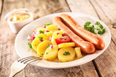Wiener sausages with baby potatoes. Two grilled Wiener sausages with baby potatoes, herbs and tomato on a white plate on a rustic wooden surface Stock Image