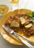 Wiener Schnitzel. Plate of wiener schnitzel meats with lemons and a glass of beer Royalty Free Stock Photography