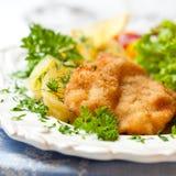 Wiener Schnitzel. Closeup of wiener schnitzel with fresh herbs and potatoes Royalty Free Stock Images