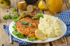 Wiener Schnitzel, delicious schnitzel. Wiener Schnitzel, served with baked potatoes, pickled cucumbers and freshly squeezed orange juice Stock Photography