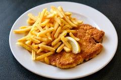 Wiener Schnitzel with fried potatoes stock images