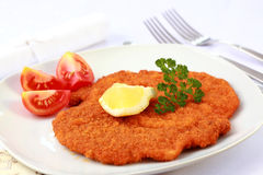 Wiener Schnitzel with lemon. Delicious Wiener Schnitzel with lemon and tomatoes Royalty Free Stock Image