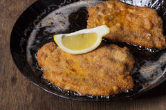Wiener schnitzel. In a pan on wood Stock Images