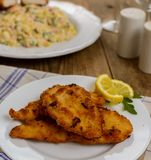 Wiener schnitzel with potato salad. Czech traditional schnitzel with potato and vegetables salad on wood table Stock Photo