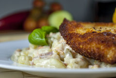 Wiener schnitzel with potato salad. Wiener schnitzel with potato and vegetables salad on wood table stock photo