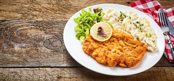 Wiener Schnitzel served on rustic table. Wiener Schnitzel served with salad, lemon and side dish on white plate with cutlery on rustic rough wooden table with Royalty Free Stock Images