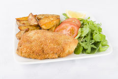 Wiener Schnitzel. Veal steak breaded and fried in butter served with salad, potato wedges and a lemon slice Royalty Free Stock Photography