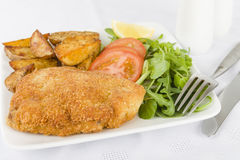 Wiener Schnitzel. Veal steak breaded and fried in butter served with salad, potato wedges and a lemon slice Stock Images