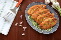 Wiener schnitzels. A plate of Wiener schnitzels on a wooden background Royalty Free Stock Photos