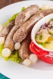 Wiener Würstchen mit Kartoffelsalat und in Essig eingelegten Zwiebeln auf einem Holztisch Lizenzfreie Stockfotos
