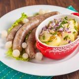 Wiener Würstchen mit Kartoffelsalat und in Essig eingelegten Zwiebeln auf einem Holztisch Stockfotografie