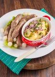 Wiener Würstchen mit Kartoffelsalat und in Essig eingelegten Zwiebeln auf einem Holztisch Stockfoto