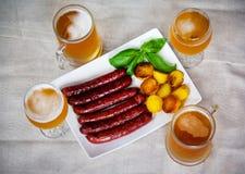 Wieprzowin kiełbasy, szkła piwo, piec grule Selekcyjna ostrość Zdjęcie Stock
