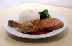 Wieprzowina kotlecika stku biali ryż i zieleni brokuły w naczyniu na drewnianym stole Obrazy Stock