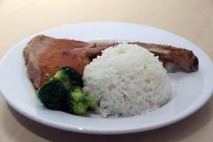 Wieprzowina kotlecika stku biali ryż i zieleni brokuły w naczyniu na drewnianym stole Zdjęcie Stock