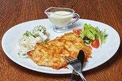Wieprzowina kotleciki piec w serze, brokuły, czereśniowi pomidory, sałata oliwki i kwaśna śmietanka, słuzyć na białym talerzu zdjęcie stock