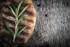 Wieprzowina stek z rozmarynami i pieprzem na starym drewnianym stole stonowany Zdjęcia Royalty Free