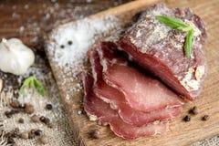Wieprzowina suszył mięsnych plasterki na nieociosanym ciemnym drewnianym tle Wysuszony wieprzowiny prosciutto salami baleron z zi obrazy royalty free