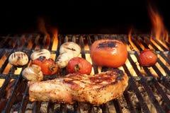 Wieprzowina ziobro stek, pomidor I pieczarki Na Gorącym BBQ grillu, Obrazy Stock