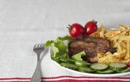 Wieprzowiny mięso na grillu z smażącymi świeżymi warzywami i grulami Fotografia Stock