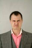 Wierd grimace. Portrait of man in suit makig funny face Stock Images