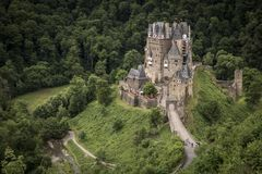 WIERSCHEM, GERMANY,  JUNE 30, 2017: The Burg Eltz and the Elzbach. WIERSCHEM, GERMANY,  JUNE 30, 2017: The Burg Eltz, the Elzbach and a small group of visitors Stock Image