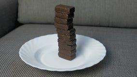 Wierza czekoladowi cukierki na białym talerzu na kanapie Pojęcie niezdrowy łasowanie zbiory