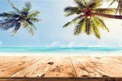 Wierzchołek drewno stół z zamazanego morza i kokosowego drzewa tłem Fotografia Stock