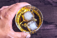 Wierzchołek widok trzyma szkło whisky z kostkami lodu na drewno stołu tle mężczyzna, ostrość na kostkach lodu Zdjęcia Stock