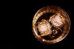 Wierzchołek widok whisky w szkle z kostkami lodu na czarnym tle, ostrość na kostkach lodu Obrazy Stock