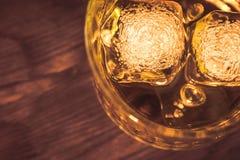 Wierzchołek widok whisky w szkle z kostkami lodu na drewno stołu tle, ostrość na kostkach lodu Obrazy Royalty Free
