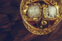 Wierzchołek widok whisky w szkle z kostkami lodu na drewno stołu tle, ostrość na kostkach lodu Obraz Royalty Free