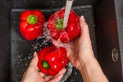 Wierzchołka puszka widok na czarnym zlew z rękami myje czerwoną dzwonkową paprykę Obraz Royalty Free