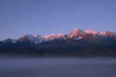 Wierzchołki góry błyska powstającym słońcem Zdjęcia Stock