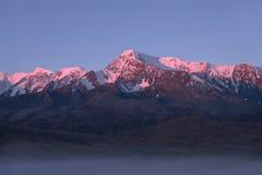 Wierzchołki góry błyska powstającym słońcem Zdjęcia Royalty Free