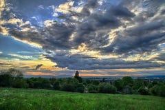 Wiese mit drastischen Wolken am Hintergrund lizenzfreie stockbilder