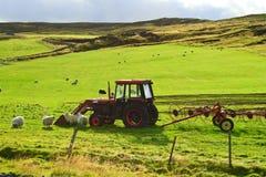 Wiese mit einem Traktor Stockfotos
