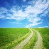 Wiese mit Schotterweg und Himmel Stockfotos
