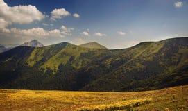 Wiese umgeben durch Hügel Lizenzfreie Stockfotografie