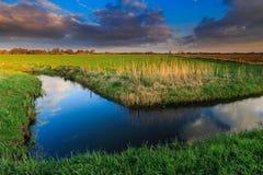 Wiese und Abzugsgraben bei Sonnenuntergang Lizenzfreie Stockfotografie