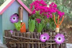 Wiese voll des gelben Löwenzahns Gartenarbeitwerkzeuge und Frühlingsblumen Lizenzfreie Stockbilder