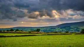 Wiesen und Wolkenbildung über Abstandshügeln Lizenzfreies Stockfoto