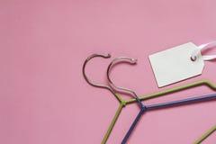 Wieszaki dla ubrań i etykietka na różowym tle Sprzedaż, rabat, handlowy pojęcie Zdjęcie Stock