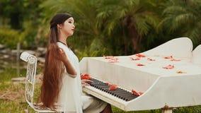 Wietnam dziewczyna z długim czarni włosy outdoors bawić się pianino Liście klonowi rozpraszający na kluczach autumn buty deszczow zbiory wideo
