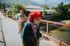 wietnamczyk kobiety niesie kosze i odprowadzenie na moscie w Sa Pa, Wietnam zdjęcie stock