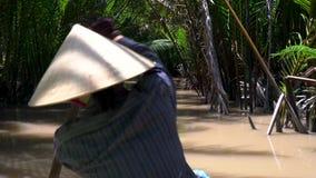 Wietnamska kobieta jest ubranym liścia kapelusz i paddling łódź tradycyjnego czółno w Mekong delcie lub, Wietnam