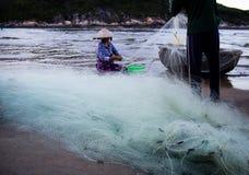 Wietnamska rybaczka z conical kapeluszowym sprawdza ona dla chwyt ryba od plaży sieci zdjęcie stock