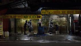 Wietnamskie młodego człowieka obmycia hulajnoga przy nocą w ulicznym domyciu robią zakupy w Ho Chi Minh mieście obrazy stock